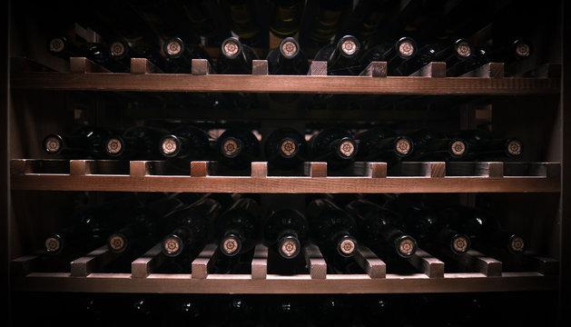 bottles of wine lie on wooden shelves