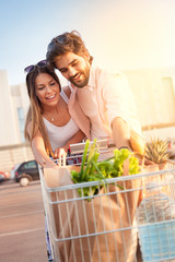 Smiling couple with shopping cart full of groceries