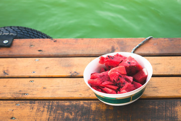 summer refreshment cold sliced watermelon in a bowl on wooden dock by the river