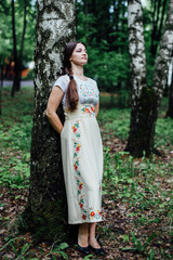 Girl in traditional Russian dress sarafan leaned against birch