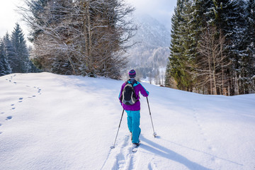 Hiker with snowshoes on snow trail in winter landscape of forest in Oberstdorf, Bavaria Alps in South of Germany. Beautiful landscape with coniferous trees and white snow. Winter sport activity.