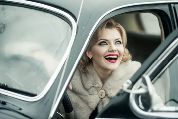 Sexy woman in fur coat sitting in retro car.