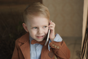 Beauty smiling child boy hand holding mobile phone or talking smartphone