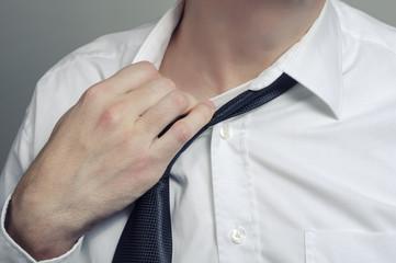 Man in white shirt taking off necktie