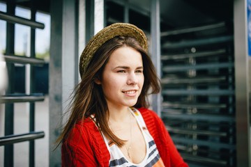 Portrait of a beautiful, stylish young Caucasian woman with a toothy smile, long developing hair in the wind and a straw hat on her head. Dressed in a red sweater and striped blouse