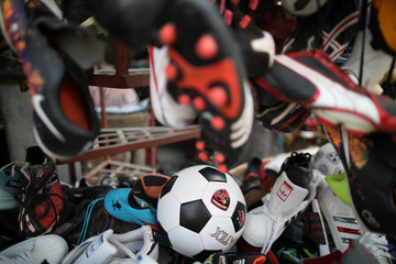 A ball is seen among sport and football shoes in a stand of a public market in Port-au-Prince
