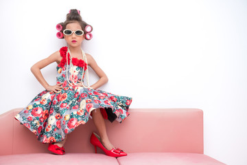 Young super model girl portrait. Pre teen girl dress up like a super model portrait. High heel red shoes, white sunglasses. Confident pose.