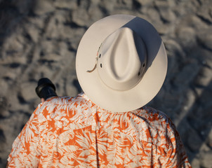unknown photographer wears a hat to keep the sun from his camera