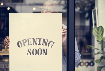 Man putting on store opening soon sign Fototapete