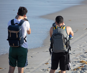 unknown photographers pause to get a shot while exploring the beach scenery