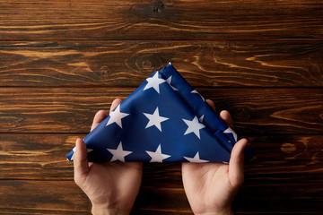 cropped shot of man holding folded united states flag on wooden background
