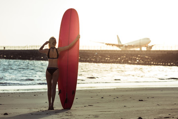 rear view of female surfer posing with surfboard on beach