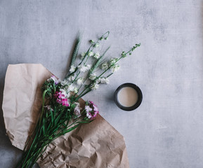 wild flowers and cup of milk. flowers and milk on textured background. flower flatlay.