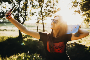 Cute caucasian girl doing a selfie holding a skateboard on her shoulders and wearing sunglasses against the sunset light.