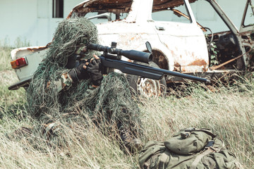 Sniper in urban combat training. Full ghillie camo suit and a high power sniper rifle. In urban combat training ground. Ready his weapon.