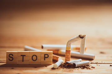 World No Tobacco Day, May 31. Close up Broken cigarette with STOP text on Wooden Block on wooden table background.