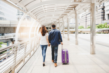 A handsome boyfriend or traveler man hold his girlfriend's hand and walk together. They love journey at foreign country. They love jeans fashion. Guy drag suitcase. They have enjoy the trip with space