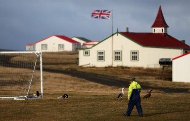 A man walks as a Union Jack flag is seen in the background in Goose Green, Falkland Islands
