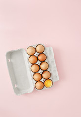 Chicken egg half broken among eggs carton pink background top view flat lay