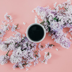 Flat lay cup coffee branches lilac flowers pink background Top view spring minimal concept