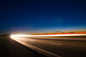 The asphalt road in the countryside with the light passing through it at the speed of cars on long exposure Wall mural