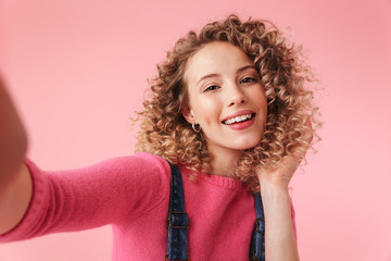Portrait of happy young girl with curly hair taking a selfie Wall mural