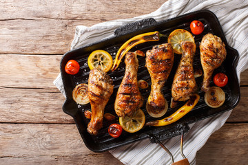 Freshly cooked grilled chicken drumstick legs with vegetables in a grill pan close-up. horizontal top view