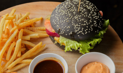 Black burger on a wooden background with potatoes and sauce