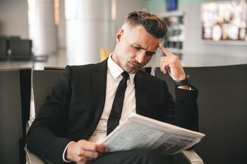 Pensive businessman reading newspaper
