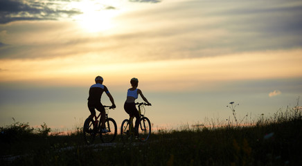 Rear view of a couple of cyclists riding along the road among the grass with wildflowers under the magical evening sky at sunset. The guys are dressed in sports clothes and helmets. Copy space