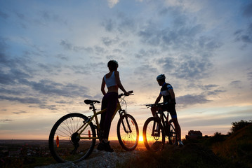 Two young sports people on mountain bikes stand on rock on top of hill looking at the sun at sunset. Girl and guy dressed in helmets and sportswear stand facing each other under evening sky