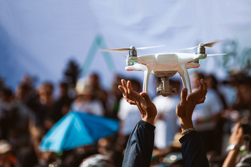 Young operator holding drone above crowd, before working with covering an event