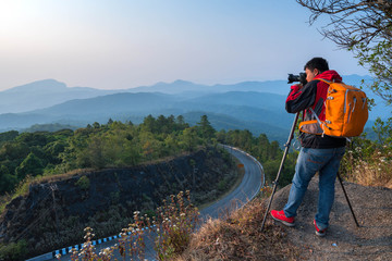 Asian Man traveler take photo view mountain of doi inthanon national park with mirrorless camera