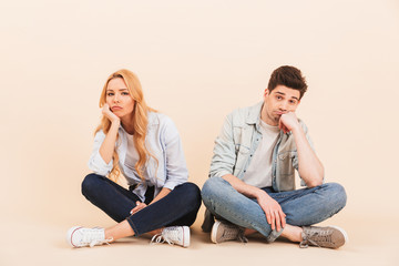 Image of dissatisfied man and woman sitting on the floor with legs crossed and propping their heads after fight or quarrel, isolated over beige background