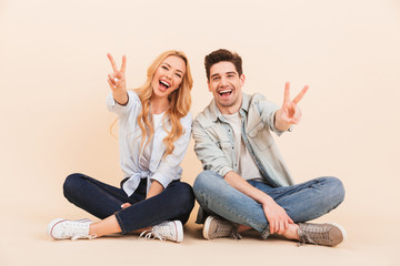 Image of happy two friends man and woman in casual clothing sitting on the floor with legs crossed and showing victory sign, isolated over beige background