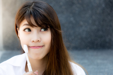 Portrait pretty young woman: Attractive girl holds toothbrush. Lovely girl looks at copy space and thinking and acts like a admiring brand, product, goods or service that make her smile and happy Wall mural