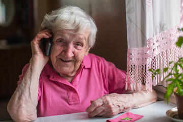 Elderly woman talks on a mobile phone sitting at home.