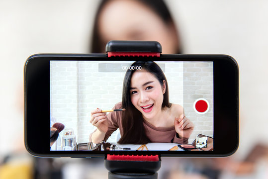 Beautiful Asian woman beauty vlogger recording make up tutorial video by smartphone