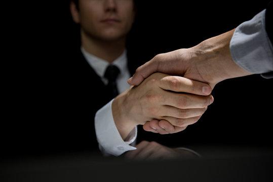 Business partners making handshake in dark shadow