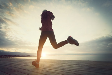 Healthy lifestyle, sports woman running on wooden boardwalk sunrise and sea seaside