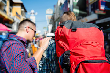 Two tourist backpacker friends finding direction to their destination while traveling in Khao San road, Bangkok Thailand