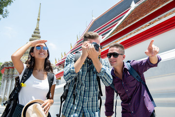 Group of young tourist backpacker friends at Thai temple on summer vacation traveling in Bangkok Thailand