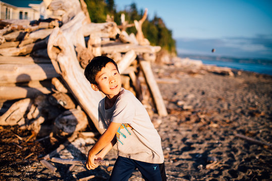 Boy playing with stick and rock on beach