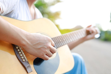 Male playing acoustic guitar in the nature.