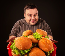 Fat man eating fast food hamberger and carries treat for friends on tray. Breakfast for overweight person. Comfortable clothes for work. Fatso with tray of harmful food. Mass obesity due to poor foods