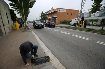 """A member of Granoller's Committee for the Defence of the Republic spray paints a slogan reading """"We are a Republic"""" as part of an protest to demand the release of jailed Catalonian politicians in Granollers"""