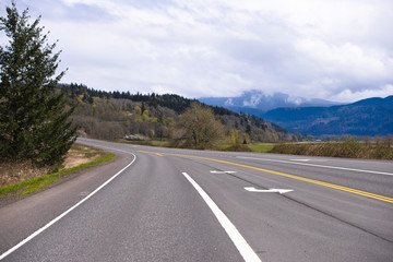 Wide multi-lane road with markings passes through picturesque Columbia Gorge area with meadow forest and mountain