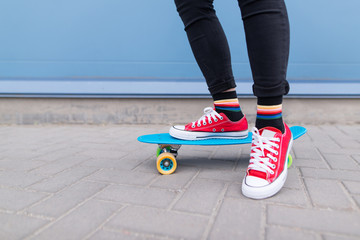 Close-up of a girl's legs in red sneakers standing on a blue skate on the background of a blue wall. Hipster girl on a skateboard. Street style