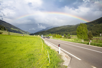 Rainbow above road and mountains