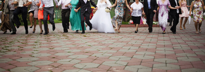 Newlyweds and guests of the wedding walking along the park together